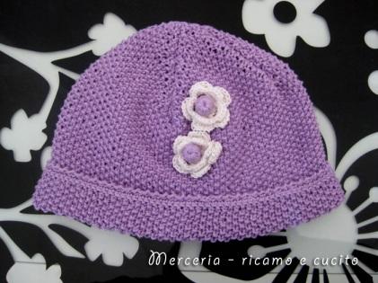 Cappellino-neonato-fatto-ai-ferri-con-fiori-all'uncinetto-1