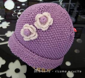 Cappellino-neonato-fatto-ai-ferri-con-fiori-all'uncinetto
