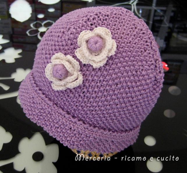 Cappellino neonato fatto ai ferri con fiori all'uncinetto