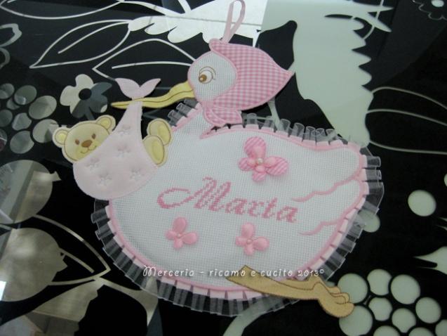Fiocco nascita cicogna rosa, bustina portaoggetti pois e bavetta per Marta